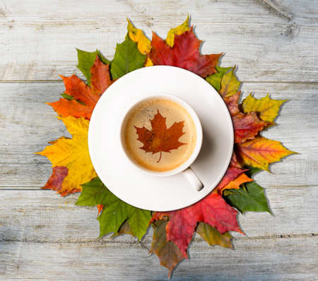 Photo pour Coffee cup with maple symbol on autumn colorful leaves on wooden table, top view - image libre de droit