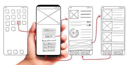 Foto de UI development. Male hand holding smartphone with wireframed user interface screen prototypes of a mobile application on white background. - Imagen libre de derechos