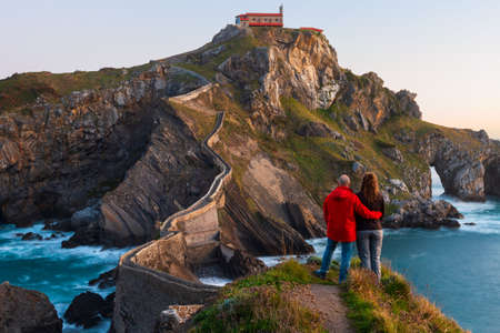 Foto de Couple against San Juan de Gaztelugatxe, its medieval stairs and bridge at sunrise, Basque Country, Spain - Imagen libre de derechos