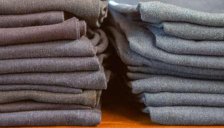 Foto de pile of denim jeans of different colors. in store on wooden shelf - Imagen libre de derechos