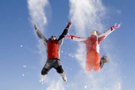 Young couple playing with snow outdoor in a sunny day