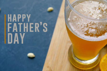 Foto de Happy father's day graphic with pint of beer and snacking peanuts in background.  Text for holiday card or banner on black background. - Imagen libre de derechos
