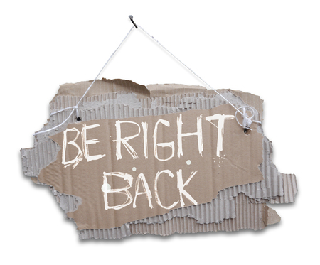 Foto de Cardboard sign on a cord with a words BE RIGHT BACK.  Ripped, corrugated paper hanging on cord with white sign BE RIGHT BACK.Isolated on white background. - Imagen libre de derechos