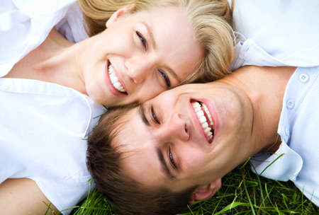 Happy couple lying on a meadow in summer