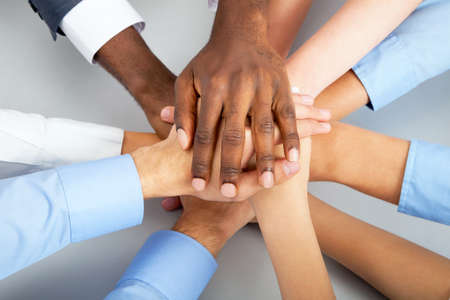 Foto de Closeup of business team putting their hands on top of each other - Imagen libre de derechos