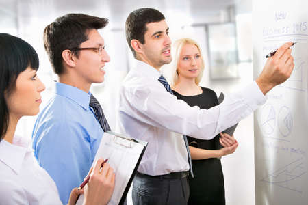 Photo pour Group of business people looking at the graph on flipchart - image libre de droit