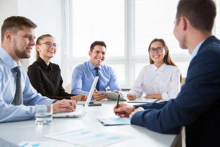 Foto de Group of business people at a meeting around a table in a modern office - Imagen libre de derechos