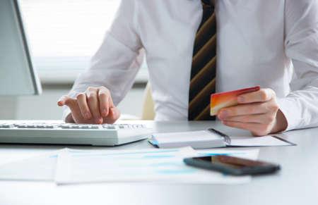 Foto de Businessman holding credit card and using laptop. Online payd. - Imagen libre de derechos