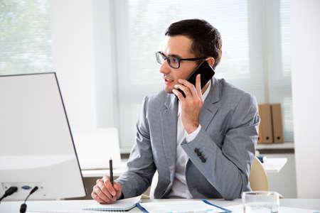 Foto de Young handsome businessmantalking on the phone in an office - Imagen libre de derechos