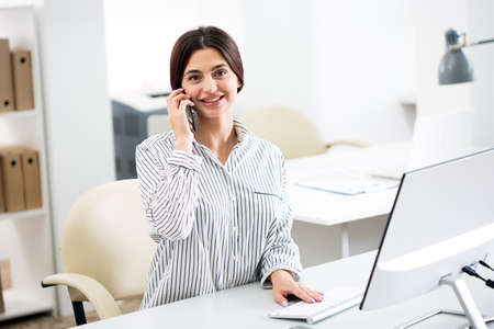 Photo for Pretty business woman talking on the phone in the office - Royalty Free Image