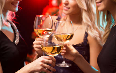 Photo for Beautifully dressed young girls with glasses of wine at a Christmas party - Royalty Free Image