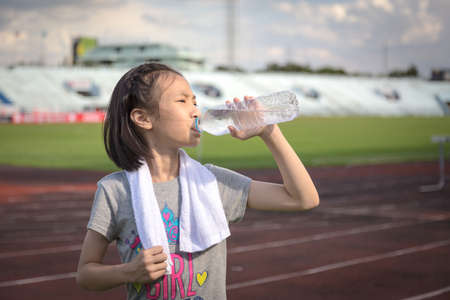 Photo for Asian girl drinking water from plastic bottle after jogging, little girl drink thirsty water due to hot weather after run in the racetrack - Royalty Free Image