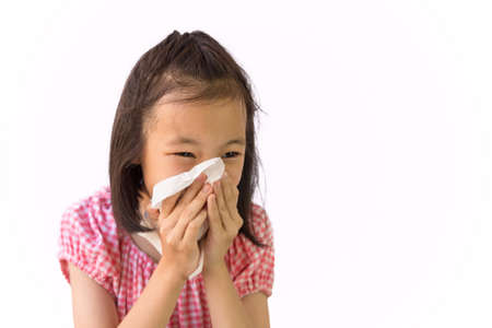 Foto de Portrait of cute little girl blowing nose in paper handkerchief,Asian girl sneezing in a tissue isolated on white background,hay fever, runny nose,concept of pollution,dust allergies - Imagen libre de derechos