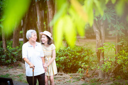 Foto per Asian little girl supporting senior woman with walking stick,happy smiling grandmother and granddaughter in the park,elderly people walking exercise for health,concept family;summer and vacation - Immagine Royalty Free
