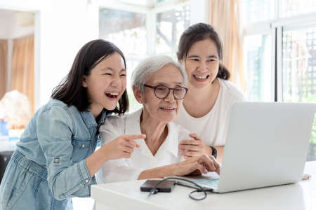 Foto de Mother and daughter surfing the internet;watching something interesting with grandmother,happy smiling asian senior woman while her daughter and granddaughter using laptop computer at table in home,concept family,technology - Imagen libre de derechos