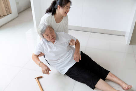 Foto de Asian elderly people with walking stick on floor after falling down and caring young woman assistant,sick senior woman fell to the floor because of dizziness,faint,suffering from illness and having a daughter to help and take care of her - Imagen libre de derechos