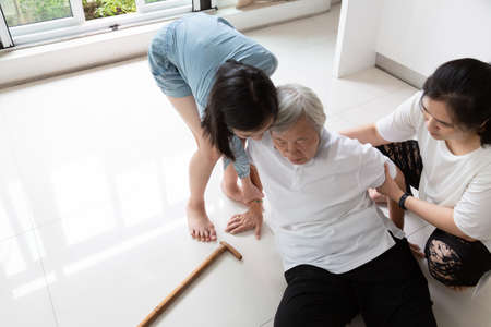 Photo pour Asian elderly people with walking stick on floor after falling down and caring young woman assistant,sick senior woman or mother fell to the floor because of dizziness,faint,suffering from illness and having a daughter,granddaughter to help and take care of her - image libre de droit