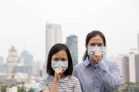 Photo pour Asian women or mother and daughter suffer from cough with face mask protection,cute child and adult woman wearing face mask because of air pollution in the city building as background,Sick girl with medical mask;concept of pollution,dust allergies and health - image libre de droit