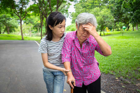 Foto de Asian senior grandmother has headache pain,touching her head with her hands,vertigo;dizziness;sick elderly people high blood pressure,feel faint,child girl or granddaughter care,help,support in outdoor - Imagen libre de derechos