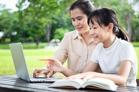 Photo pour Happy asian family,mother,daughter enjoying using laptop computer in outdoor park, female tutor or teacher working,teaching child girl how to learning,student is interested in studying having fun,tutoring school,education concept - image libre de droit