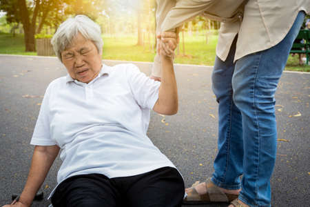 Photo pour Asian elderly woman fell to the floor after tripped over something, female caregiver or daughter help care to her in nursing home,sick senior mother skid,falling down because of dizziness,faint,suffering from illness,headache,hypertension,health care concept - image libre de droit