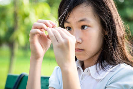 Foto per Asian beautiful child girl pulling her hair with her fingers in mental health problems,nervous system,brain system or schizophrenia,female psychiatric patient in trichotillomania hair-pulling disorder - Immagine Royalty Free