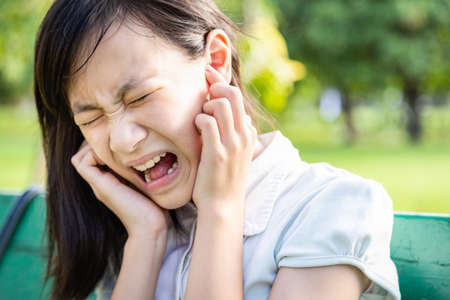 Foto de Annoyed woman covering ears with forefingers feel hurt ear ache pain otitis from loud noise sound,noisy music or anxiety asian child girl with schizophrenia not wanting to hear unpleasant things suffer from mental pain,hearing things - Imagen libre de derechos