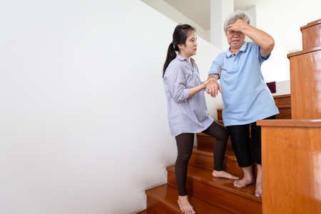 Photo for Asian senior mother having blood pressure,vertigo,dizziness while walking down the staircase,sick elderly woman headache pain,feel faint,daughter or care assistant,help,support at home,health care concept - Royalty Free Image