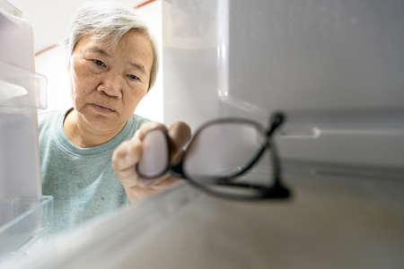 Foto de Asian senior woman with memory impairment symptoms,forget her glasses in the refrigerator or storing glasses in the fridge,female elderly having dementia, cognitive impairment, alzheimer's, amnesia - Imagen libre de derechos