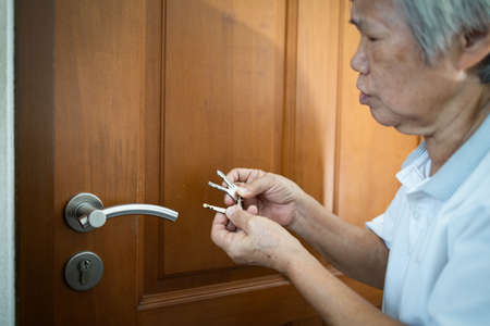 Foto de Asian senior woman is confused because she can not remember the key to opening the door of her bedroom,memory loss in elderly people,old patients with cognitive impairment,alzheimer,senile dementia - Imagen libre de derechos