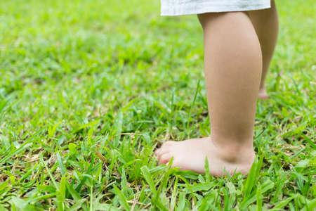 Foto für Baby's foot stepping on the grass in the morning. - Lizenzfreies Bild