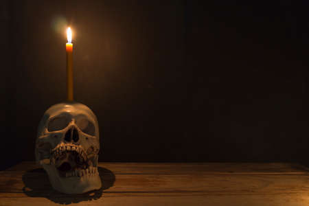 Foto de Human skull with candle light on wooden table in the dark background, Decorate for Halloween Theme with copy space. - Imagen libre de derechos