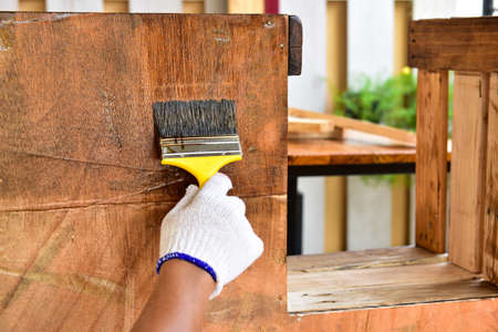 Photo for The painter uses the lacquer paint to the wooden furniture with a yellow brush. He worked with minuteness. - Royalty Free Image