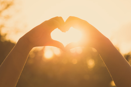 Foto de hands forming a heart shape at sunset - Imagen libre de derechos