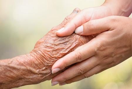 Photo pour Senior and young holding hands - image libre de droit