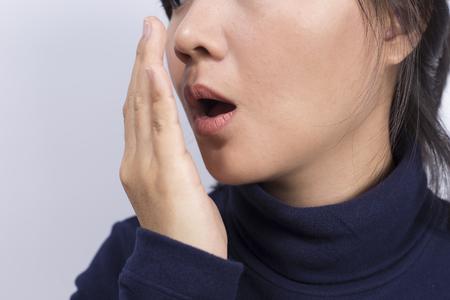 Foto de Health Care: Woman checking her breath with her hand - Imagen libre de derechos