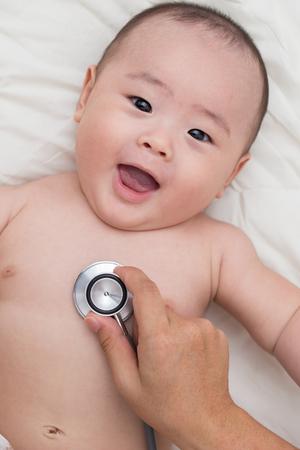 Foto für Doctor using a stethoscope to listen to baby's chest - Lizenzfreies Bild
