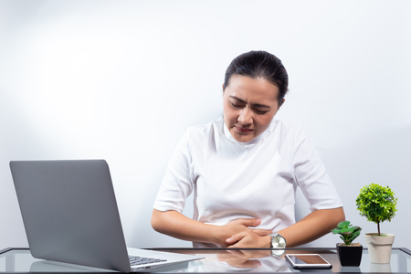 Photo pour Woman has stomach ache at office - image libre de droit