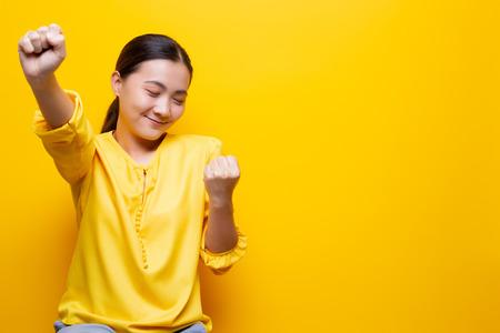 Foto de Happy woman make winning gesture isolated over yellow - Imagen libre de derechos