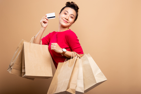 Photo pour Portrait of woman holding shopping bags and credit card isolated over background - image libre de droit