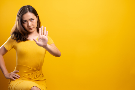 Foto de Woman making stop sign with hand on isolated yellow background - Imagen libre de derechos