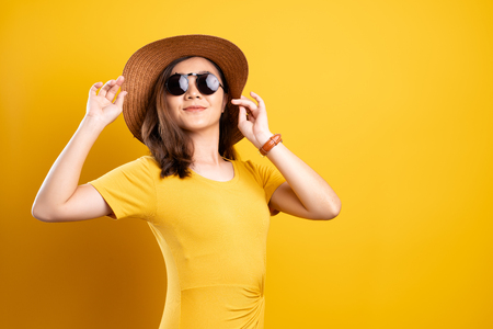 Foto de Portrait woman wearing sunglasses and hat isolated over yellow background - Imagen libre de derechos