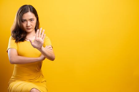 Photo pour Woman making stop sign with hand on isolated yellow background - image libre de droit