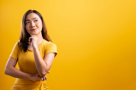 Foto de Happy woman thinking and standing isolated over yellow background - Imagen libre de derechos