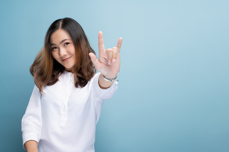 Photo for Woman in love showing love sign isolated over blue background - Royalty Free Image