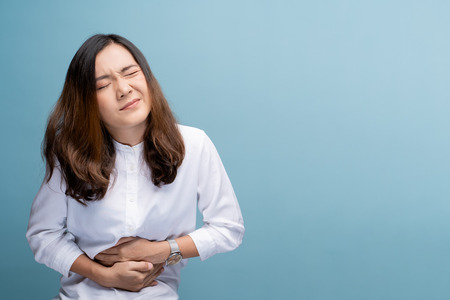 Foto für Woman has stomachache isolated over blue background - Lizenzfreies Bild