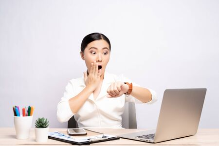 Photo pour Shocked woman holding hand with wrist watch at office isolated over background - image libre de droit