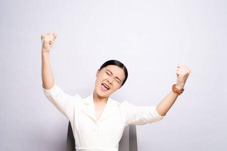 Foto de Happy woman make winning gesture sitting isolated over white background - Imagen libre de derechos