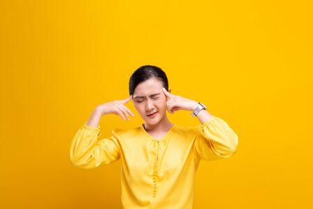 Foto für Woman has headache isolated over yellow background - Lizenzfreies Bild