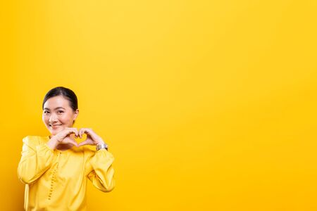 Photo for Woman in love showing heart isolated over yellow background - Royalty Free Image